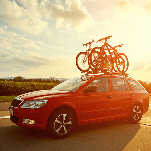 Red family sedan with a bike rack | Car Insurance