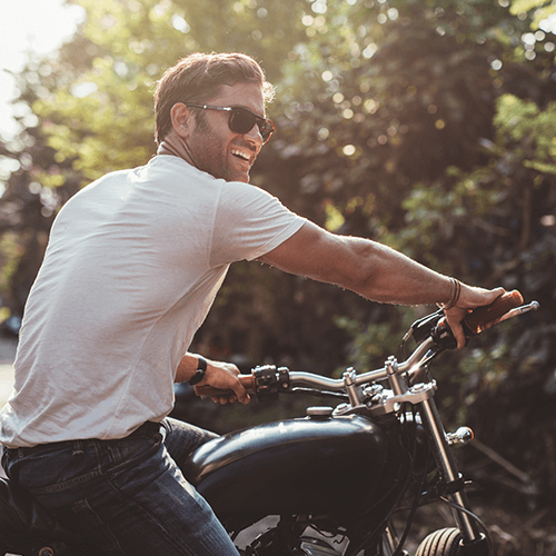 Man with a white shirt and sunglasses riding a black motorcycle | Motorcycle Insurance